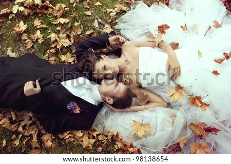 wedding theme, the bride and groom are in the maple leaves on grass - stock photo