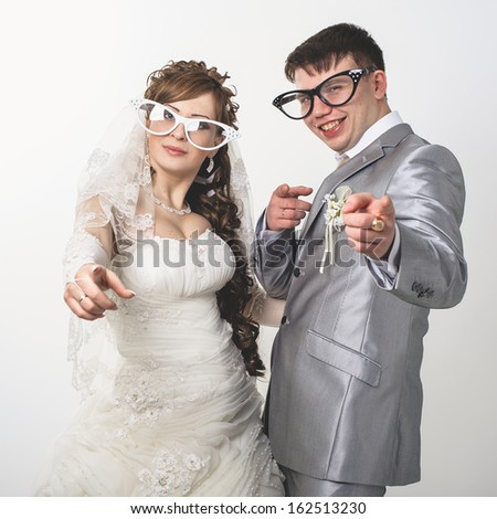 wedding theme, the bride and groom in funny glasses isolated on white background. Happy young newlyweds on wedding day. Wedding couple. wedding dress. Bridal wedding bouquet of flowers. - stock photo
