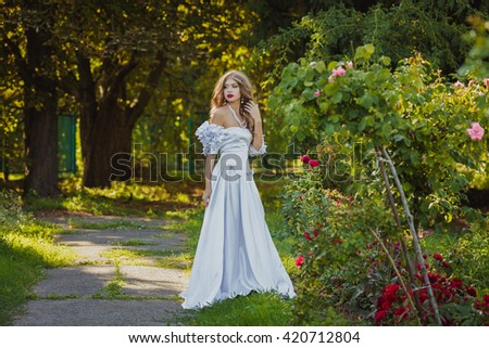 Wedding theme with flowers. Beautiful blonde bride in a luxurious white dress in garden  - stock photo
