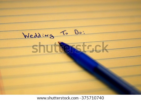 Wedding to do list written on paper with blue pen - stock photo