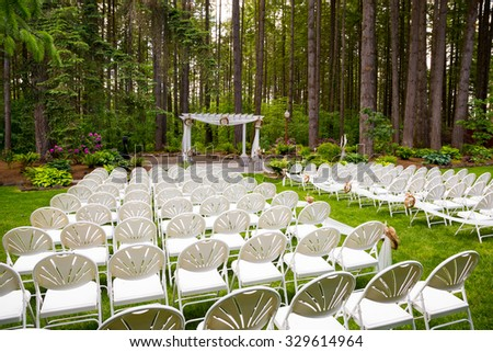 Wedding venue in Oregon has natural trees and beautiful guest seating a midst tall trees. - stock photo