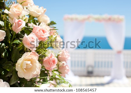 Wedding with arch and sea in background. Focus on a bouquet of roses.