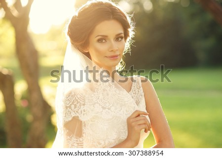 Wedding. Young beautiful bride with hairstyle and makeup posing in white dress and veil. Soft sunset light summer portrait. Girl looking in camera - stock photo