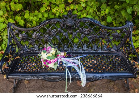 weddings bouquet on the bench in the park - stock photo