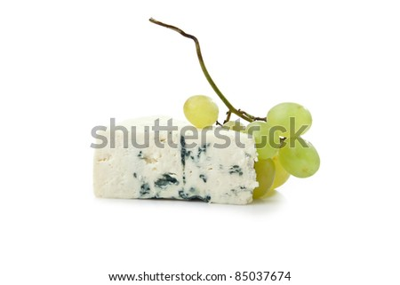 wedge of gorgonzola decorated with grapes isolated on white background - stock photo
