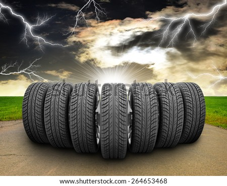 Wedge of new car wheels. Road, roadsides and grass field. Stormy sky with lightning in background - stock photo