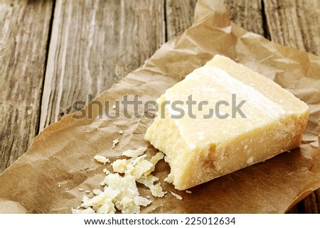 Wedge of parmigiano reggiano cheese, or parmesan, a hard granular regional cheese from Italy extensively used in italy cuisine on rumpled brown paper with some grated to show texture - stock photo