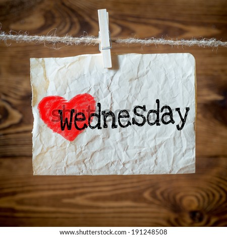 Wednesday on red heart on aged paper hanging on the clothesline. On old wood background - stock photo