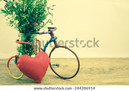 weed flowers on mini handmade bicycle in vintage color style  - stock photo