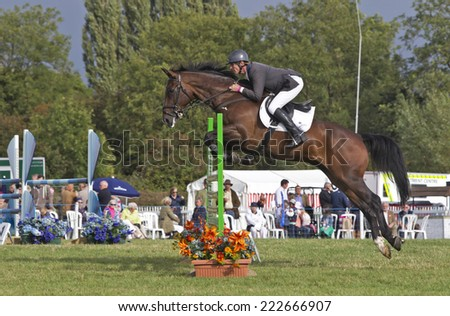 WEEDON, UK - AUGUST 28: An unnamed male rider competing in the final show jumping competition at the BCC successfully clears the gate at the Bucks County show on August 28, 2014 in Weedon