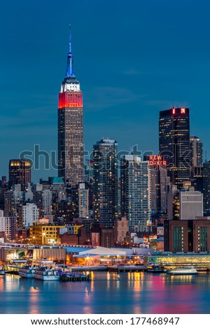 WEEHAWKEN, NJ, UNITED STATES - FEBRUARY 17, 2014: Empire State Building at dusk. The top of the iconic skyscraper displays the American flag colors, blue-white-red, in honor of Presidents' Day.