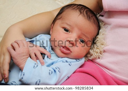 Week Old Newborn Infant gazing in direction of camera wearing blue shirt with car figures - stock photo