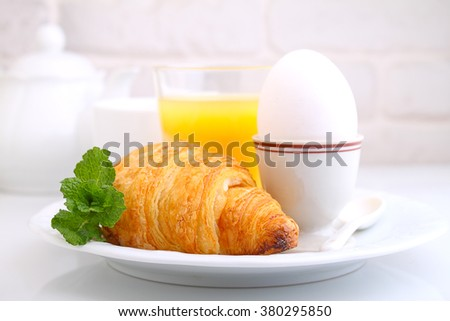 Weekend breakfast: croissants, egg and orange juice, white background