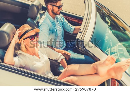 Weekend drive. Top view of smiling young woman relaxing while her boyfriend driving their convertible  - stock photo