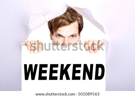 Weekend - man holding sign with the word weekend - torn ripped paper background