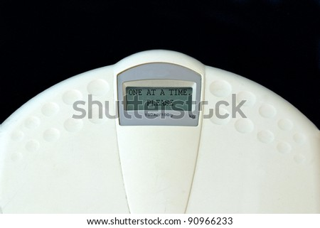 "weighing machine with ""one at a time, please"" written in the display"