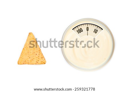 weighing scales against a bowl of dip and a nacho placed side by side