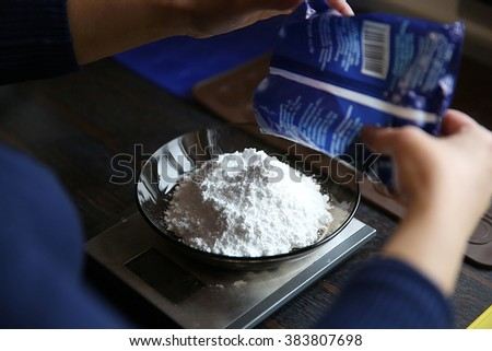 Weighing sugar powder on the digital scale - stock photo