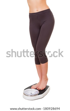 Weight control. Cropped image of young woman in sports clothing standing on weight scale