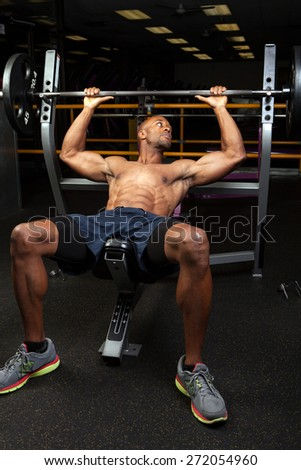 Weight lifter at the bench press lifting a barbell on an incline bench. - stock photo