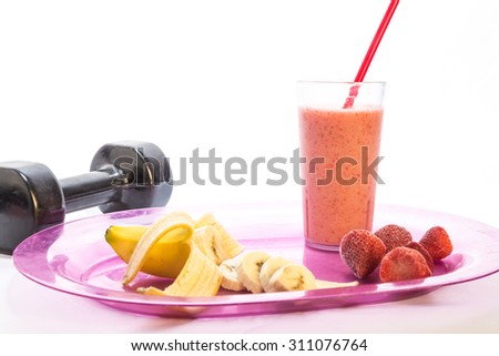 Weight Lifting equipment in background of strawberry banana fruit smoothie recovery and muscle repair drink in tall glass on white background with copy space. - stock photo