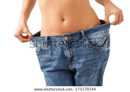 Weight loss concept - slim woman is happy to show her big old jeans.