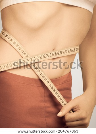 Weight loss, healthy lifestyle concept. Measuring tape on woman body, fit girl measuring her waistline, instagram filter