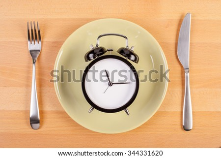 weight loss or diet concept. stock image of alarm clock on plate - stock photo