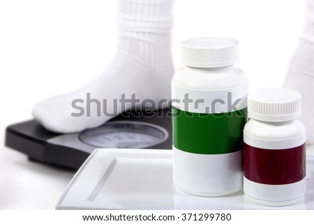 Weight loss or weight gain pill bottle with copyspace and feet on a scale.  The bottles have copyspace for logos.  The image depicts generic drugs or supplements. - stock photo