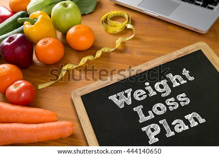 weight loss plan Fitness and weight loss concept, fruit and tape measure on a wooden table, top view - stock photo