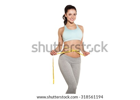 weight loss, sports girl measuring her waist, training in the gym, workout abdominals - stock photo