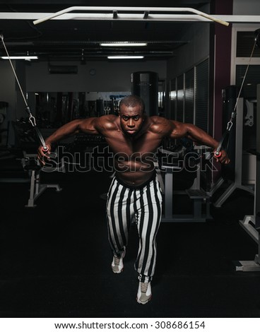 Weight training African doing bodybuilding in gym