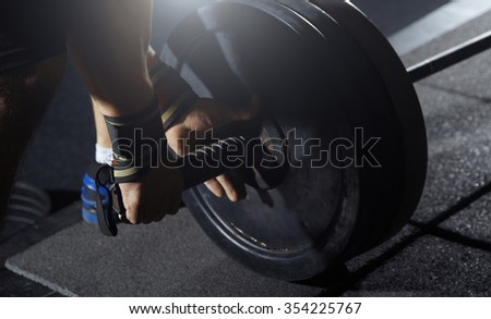 Weightlifter preparing barbell at fitness club