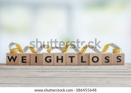 Weightloss sign with measure tape on a wooden table - stock photo