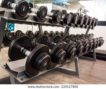 Weights, close up many black dumbbell in fitness room  - stock photo