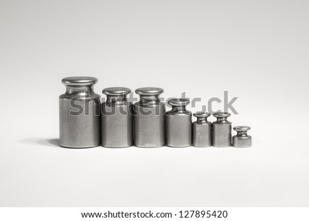 Weights isolated on white background - Calibration measuring weights set symbolizing trade, pharmacy, family, team or business teamwork - stock photo