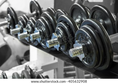Weights, many black dumbbell in fitness room - stock photo