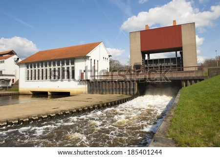 Weir and pump house with running water spill at sluice complex - stock photo