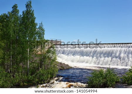 Weir owerflow of water on the man-made storage pond. - stock photo
