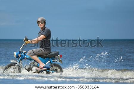 Weird biker. Strange biker on a moped driving along the seashore.  - stock photo