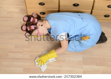 Weird wife cleaning the floor - stock photo