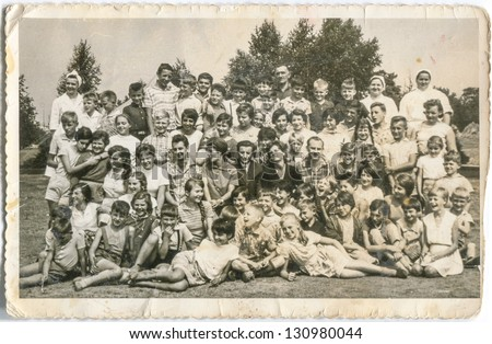 WEJHEROWO, POLAND - CIRCA 1957: a group of little boys and girls from vacation camp poses for a photo together with their tutors and kitchen staff circa 1957 in Wejherowo, Poland