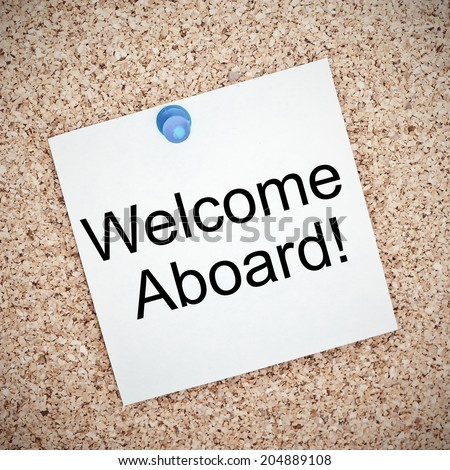 Welcome Aboard typed onto a yellow note and pinned to a cork notice board. A phrase used to welcome a new employee or team member. - stock photo