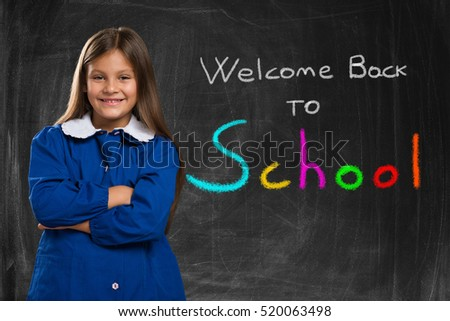 Welcome back to school. Little student standing in front of the blackboard