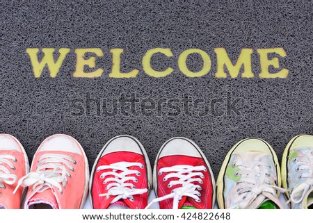 Welcome carpet with foot-ware on it  - stock photo