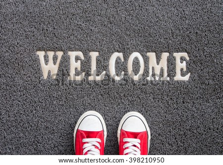Welcome carpet with red sneakers on it. - stock photo