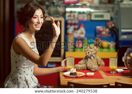 Welcome concept. Portrait of doll like brunette girl with retro hairdo in white trendy vintage polka-dot sleeveless dress drinking tea, saying hello. Close up. Copy-space. Indoor shot