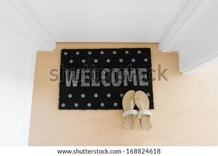 Welcome home doormat with closed door - stock photo