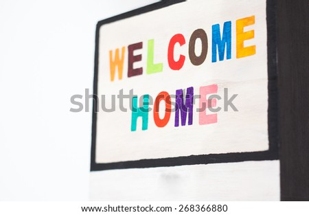 WELCOME HOME sign on wood - colorful letters - stock photo