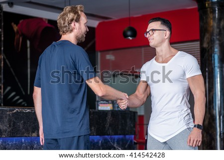 Welcome in the gym. Nice coach and client shake hands with each other before a workout in the gym - stock photo